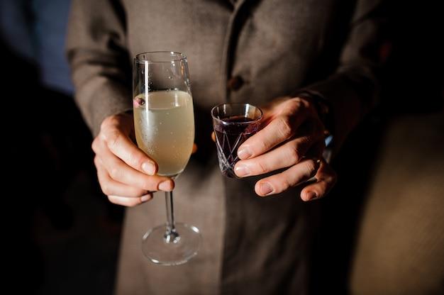 Homem está segurando um copo e uma pilha com cocktails de álcool Foto Premium