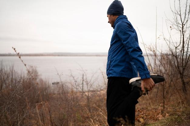 Homem esticando as pernas na floresta Foto gratuita