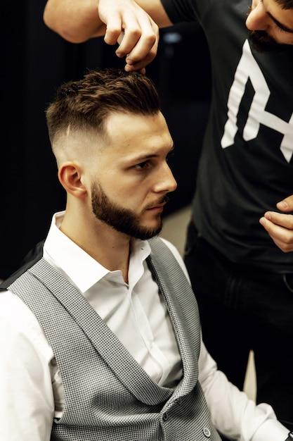Homem estiloso com uma barba ruiva em uma camisa branca e colete preto. sucesso. estilo Foto Premium