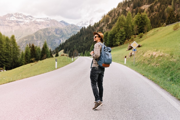 Homem estiloso de bom humor caminhando ao ar livre com uma mochila e olhando ao redor com um sorriso, aproveitando o fim de semana na itália Foto gratuita