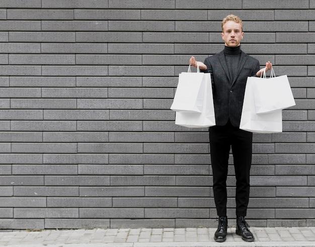Homem estiloso em preto com sacolas brancas Foto gratuita