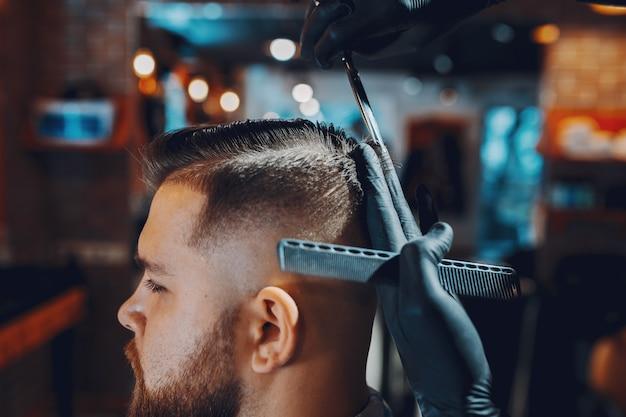 Homem estiloso sentado em uma barbearia Foto gratuita