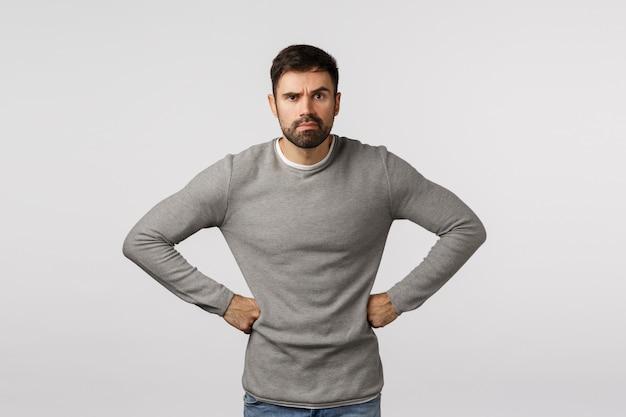 Homem estressado ou sério, irritado e mal-humorado, descontente ou sério, com barba, usa suéter cinza, segurando as mãos na cintura em pose exigente e decepcionada, franzindo a testa e fazendo careta, irritando alguém Foto Premium