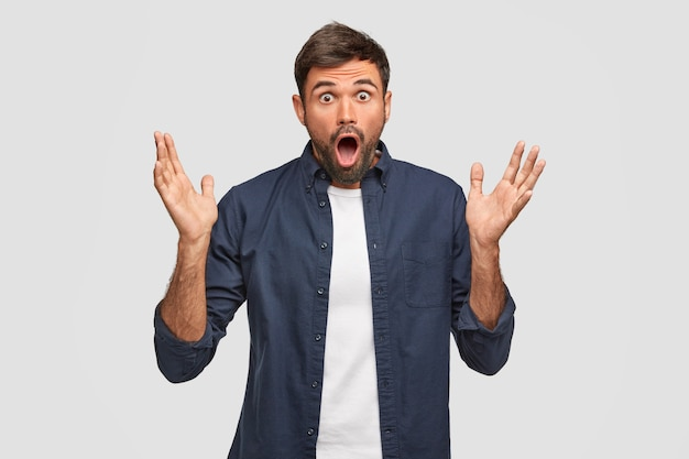 Homem europeu barbudo emotivo com expressão de espanto, gesticula com as mãos, mantém as palmas das mãos levantadas, reage a notícias repentinas, mantém o queixo caído, posa contra a parede branca. conceito de surpresa. Foto gratuita