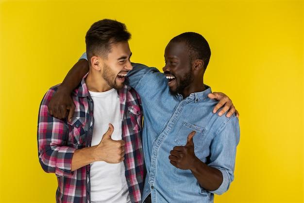 Homem europeu e africano, sorrindo e mostrando o polegar para o outro Foto gratuita