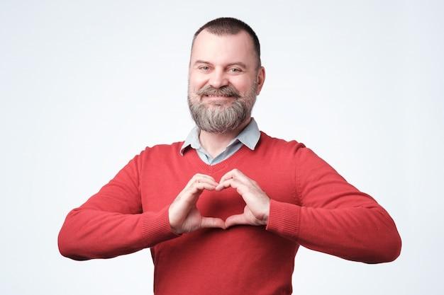 Homem europeu maduro com barba fazendo o coração das mãos Foto Premium