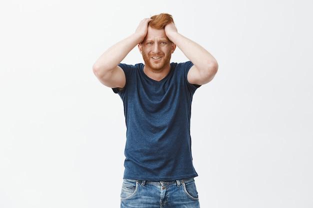 Homem europeu ruivo frustrado e chateado com problemas, segurando as mãos na cabeça, franzindo a testa e fazendo careta de tristeza e pesar Foto gratuita