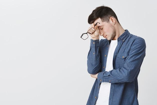 Homem exausto tirando óculos depois de muito trabalho Foto gratuita