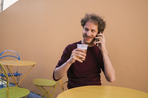Homem falando ao telefone enquanto bebia cerveja. Foto gratuita