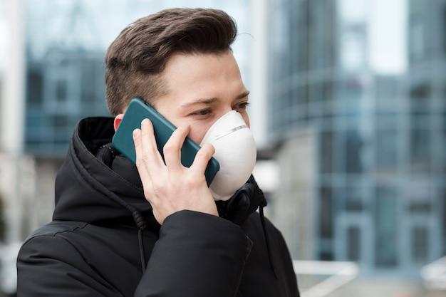 Homem falando ao telefone enquanto usava máscara médica Foto gratuita