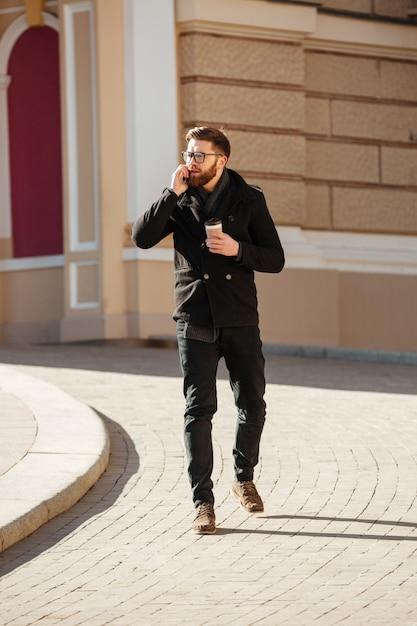 Homem falando no celular e tomando café na cidade Foto gratuita