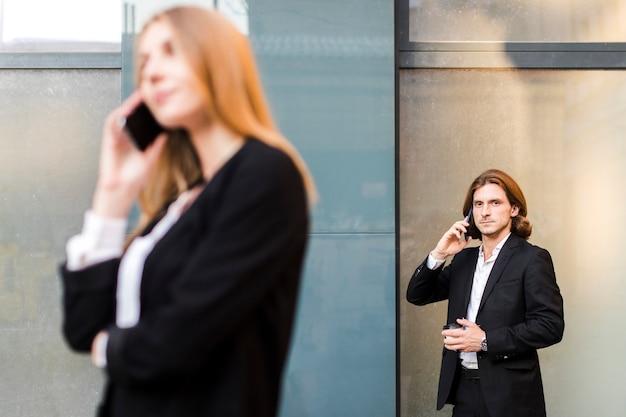 Homem falando no telefone com uma mulher fora de foco Foto gratuita