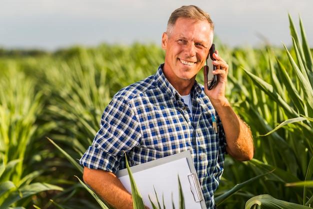Homem, falando, telefone, em, um, campo Foto gratuita