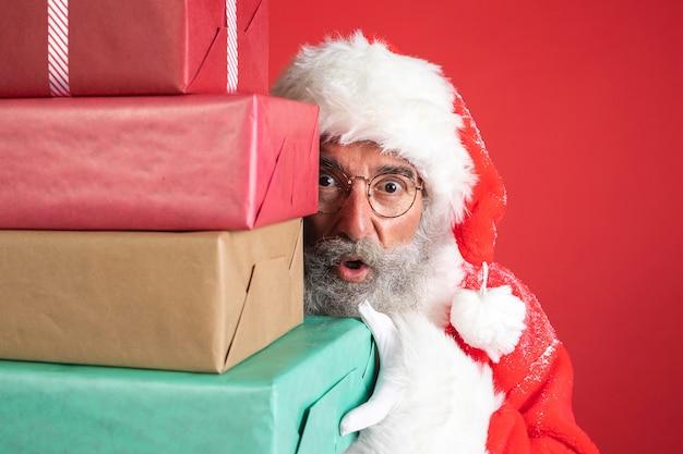 Homem fantasiado de papai noel segurando presentes Foto Premium