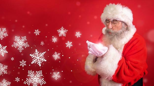 Homem fantasiado de papai noel soprando flocos de neve Foto Premium