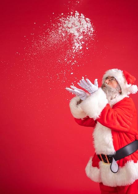 Homem fantasiado de papai noel soprando neve das mãos Foto Premium