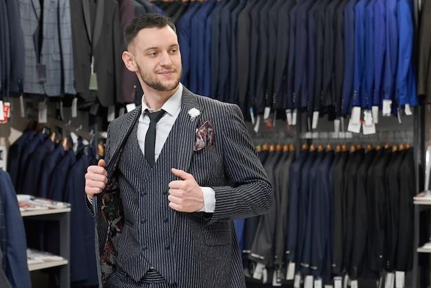 Homem fazendo compras na boutique, experimentando terno cinza elegante. Foto gratuita