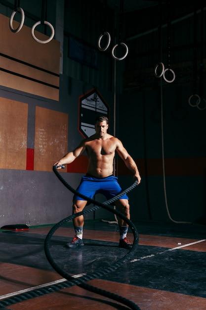 Homem fazendo crossfit com corda Foto gratuita