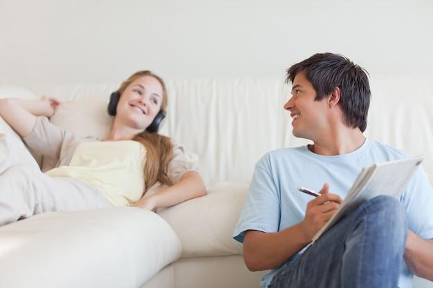 Homem fazendo palavras cruzadas enquanto sua namorada está ouvindo música Foto Premium