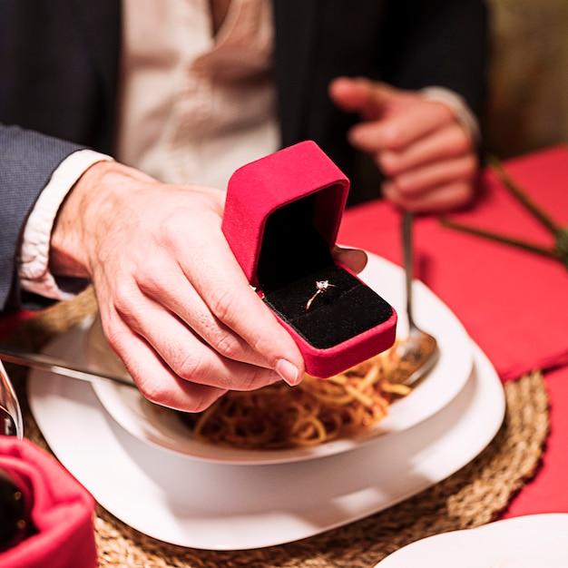 Homem fazendo proposta na mesa festiva Foto gratuita