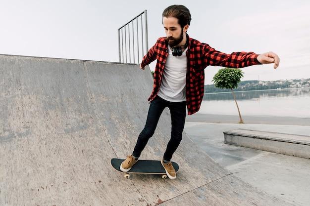 Homem fazendo truques de skate em rampas Foto gratuita
