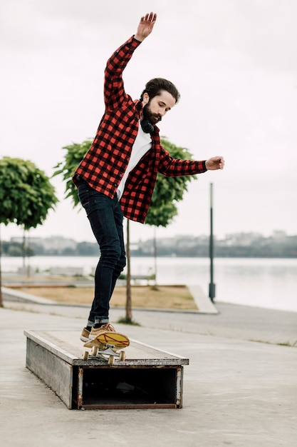 Homem fazendo truques de skate em um banco Foto gratuita