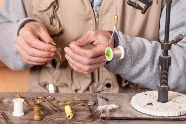Homem fazendo truta voa. voar amarrando equipamentos e materiais para a preparação da pesca com mosca. Foto Premium