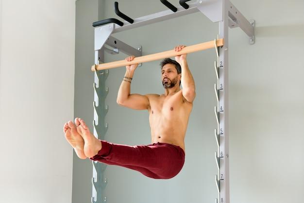 Homem fazendo um pull-up l sente-se na posição de espera Foto Premium