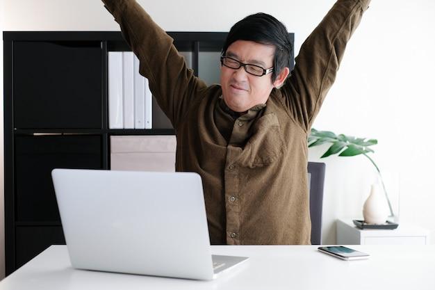 Homem fazer o corpo esticando enquanto trabalhava em escritório em casa com o telefone celular e computador portátil. Foto Premium