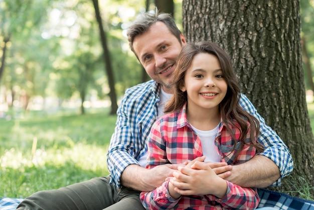 Homem feliz, abraçando a filha enquanto está sentado no parque Foto gratuita
