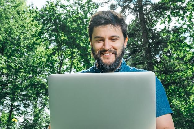 Homem feliz alegre hipster com um laptop sentado ao ar livre na grama verde Foto Premium