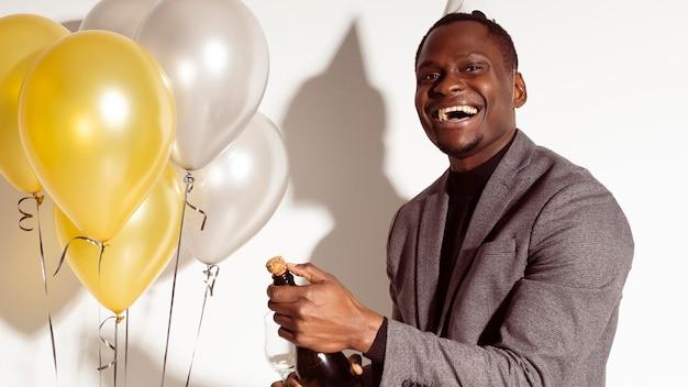 Homem feliz ao lado de balões Foto gratuita