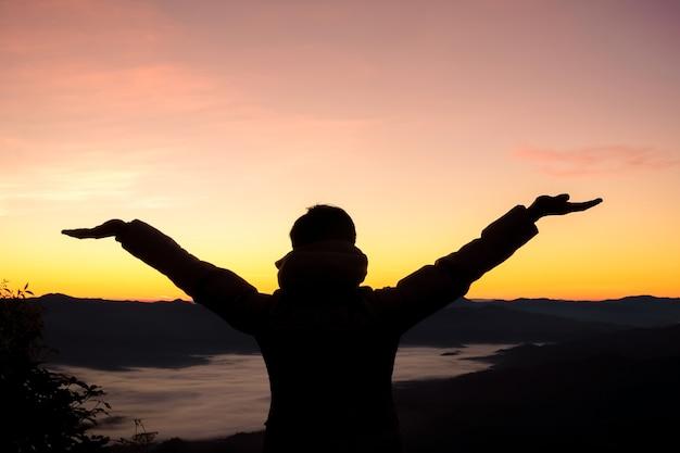 Homem feliz ao pôr do sol ou nascer do sol em pé exultante com os braços levantados Foto Premium