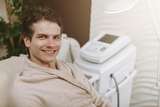 Homem feliz bonito no centro de spa Foto Premium
