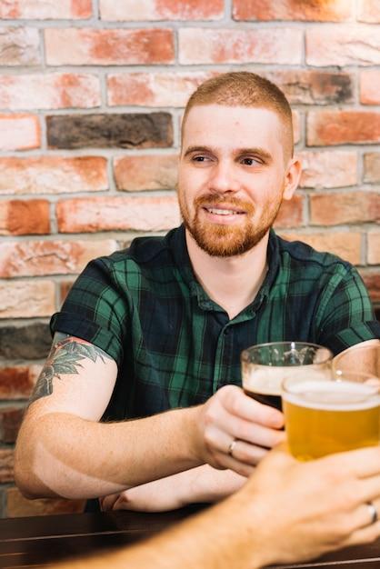Homem feliz brindando copos alcoólicos em bar Foto gratuita