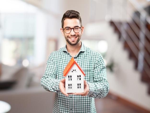 Homem feliz com a miniatura de seu futuro lar Foto gratuita