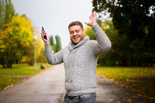 Homem feliz com as mãos no parque Foto gratuita