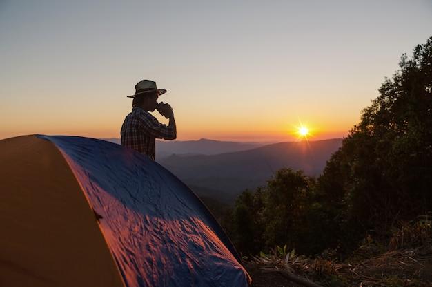 Homem feliz com bebida ficar perto da tenda ao redor de montanhas sob a luz do sol Foto gratuita