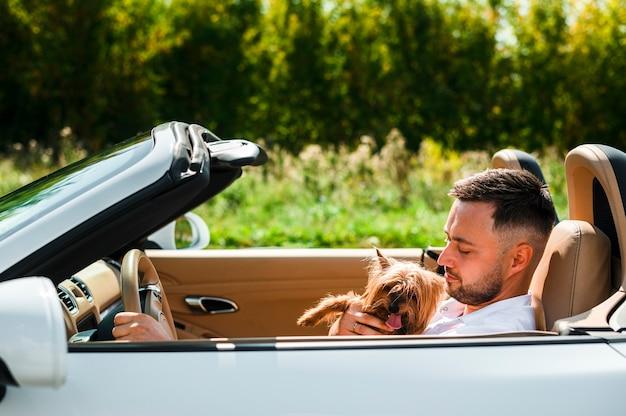 Homem feliz com cachorro viajando Foto gratuita
