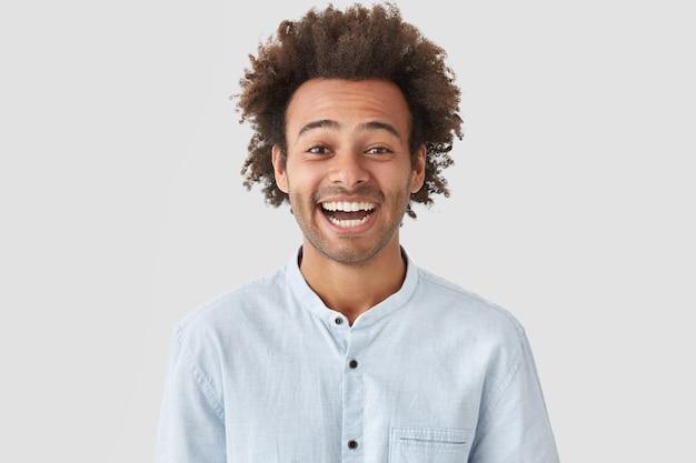 Homem feliz com expressão alegre, sorriso perfeito e dentes brancos, ri de algo engraçado Foto gratuita