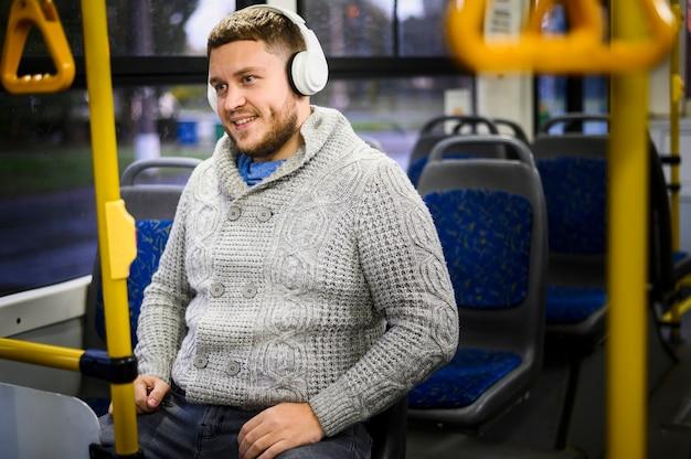Homem feliz com fones de ouvido, sentado em um banco de ônibus Foto gratuita