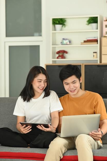 Homem feliz com namorada sorridente relaxando no sofá em casa Foto Premium