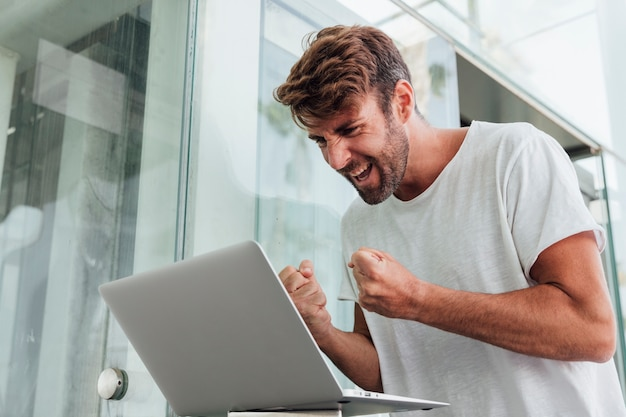 Homem feliz comemorando com notebook Foto gratuita