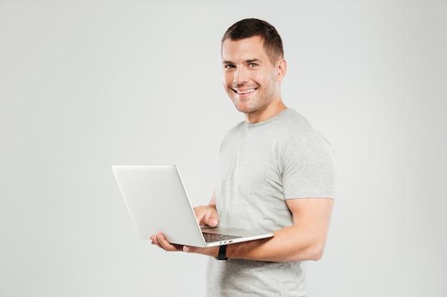 Homem feliz conversando pelo computador portátil. Foto gratuita
