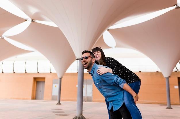 Homem feliz dando cavalinho para sua namorada Foto gratuita