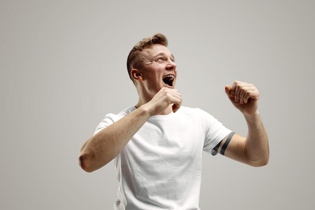 Homem feliz de sucesso vencedor comemorando ser um vencedor. imagem dinâmica do modelo masculino caucasiano em fundo cinza do estúdio. vitória, conceito de prazer. conceito de emoções faciais humanas. Foto gratuita