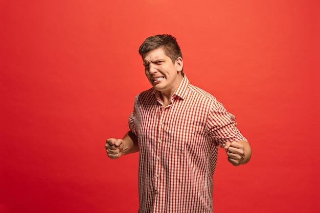 Homem feliz de sucesso vencedor comemorando ser um vencedor. imagem dinâmica do modelo masculino caucasiano em fundo vermelho do estúdio. Foto gratuita