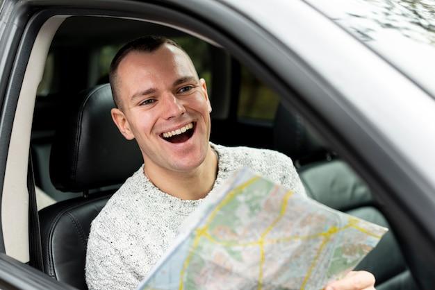 Homem feliz dirigindo e segurando um mapa Foto gratuita