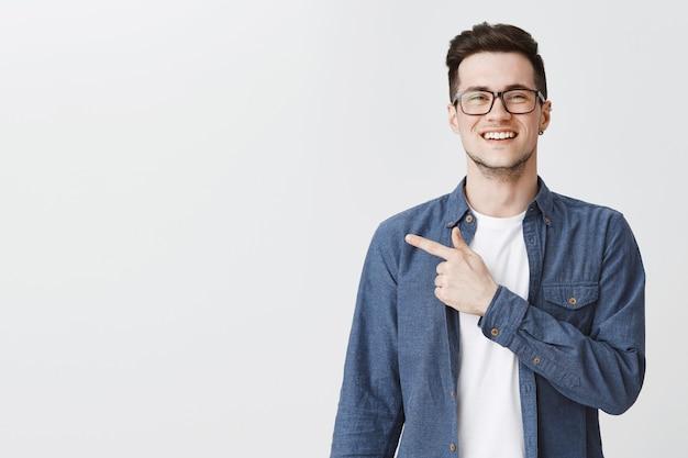 Homem feliz e bonito de óculos apontando o dedo para a esquerda Foto gratuita