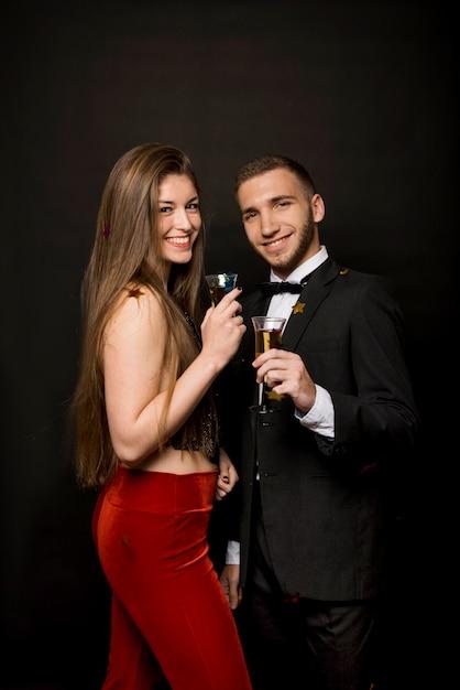 Homem feliz e mulher com copos de bebidas e confetes Foto gratuita